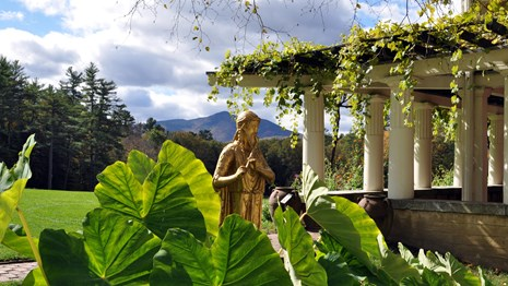 A gold statue behind leafy foliage, with a colonnade and mountain in the distance