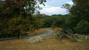 A cannon stands behind a low stone wall in a rural landscape of wooded areas and open grass