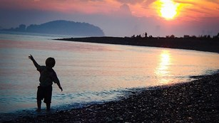 A boy dances on the beach with a sunset in the background.