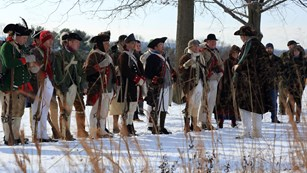 A line of people in Revolutionary War clothing