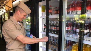 A man in a tan uniform looks at a cooler with beverages.