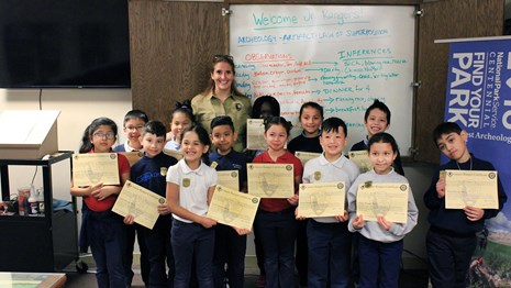 Group of elementary students displaying their junior ranger certificates in front of a whiteboard