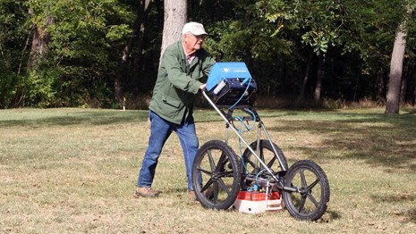 Volunteer operating ground-penetrating radar equipment in a clearing with trees in the background