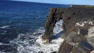 Black Hōlei Sea Arch reaching out of the ocean