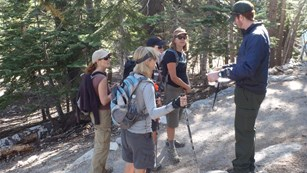 A survey is being administered along a trail in Yosemite.