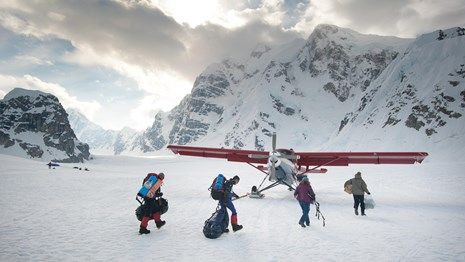 A group loads gear onto a commercial plane in Denali National Park and Preserve.