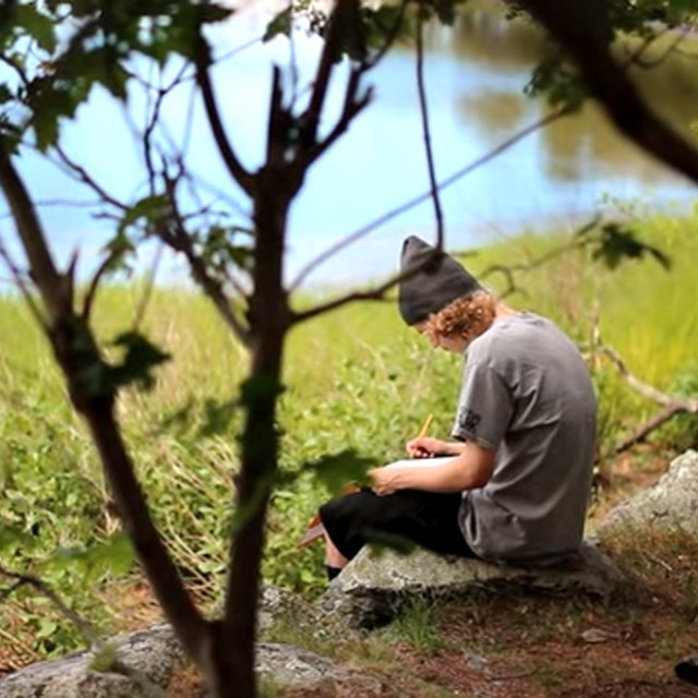young man sitting on rock next to river writing in notebook