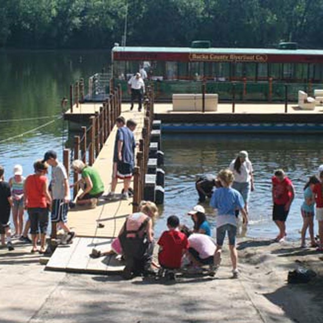 many children gathering at a dock with boat anchored to it on Lower Delaware River