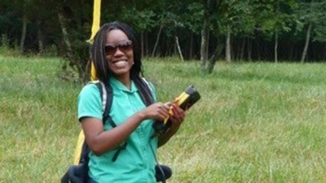 Black woman in grassy field, GPS unit in hand and large backpack with tech device on back