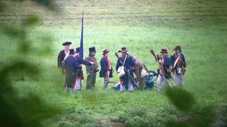 Group of reenactors in blue coats, white breeches & tricorn hats in grassy field by cannon