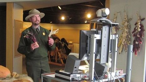 Ranger holding up props in front of a computer and camera