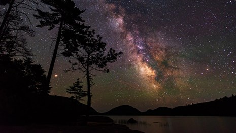 Milky way over a lake with silhouetted trees and mountains