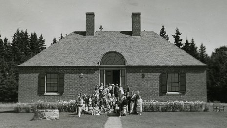 Historic photograph of a brick building with people grouped in front