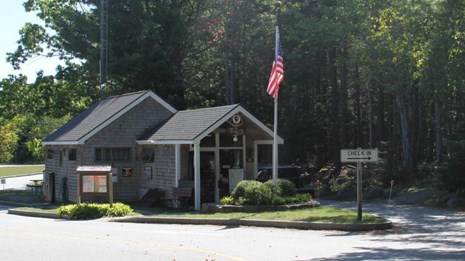 A ranger station with a flag pole and driveways leading up to it
