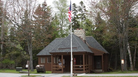 A wooden ranger station with a flag pole and driveways leading up to it