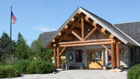 A wooden ranger station with a flag pole and patio style entrance