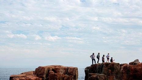 Five people on rock cliff near ocean