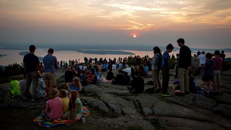 Crowds gather for sunrise on a mountain summit