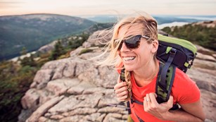 Woman wearing backpack and sunglasses smiles on mountain summit with wind in blowing across her face