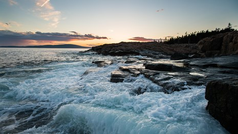 Waves crash against rocky coastline at sunset