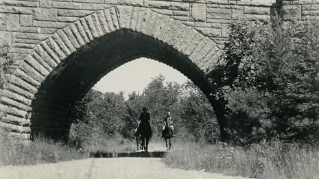 Two people riding horseback under stone bridge