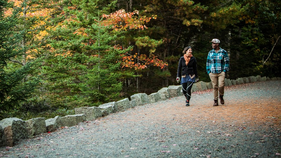 Woman and man walk along gravel carriage road under fall colors
