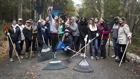 Young people with landscaping equipment participate in Take Pride in Acadia Day