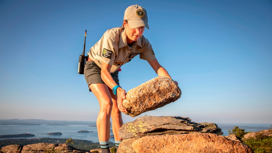 Woman stacks a rock for a trail marking cairn on a mountainside
