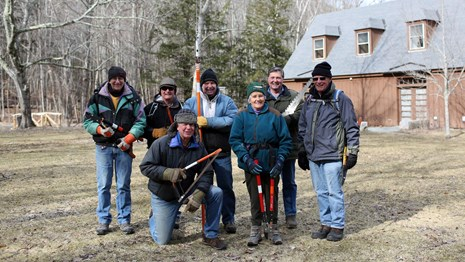Seven volunteers with saws and pruning tools outside a Nature Center