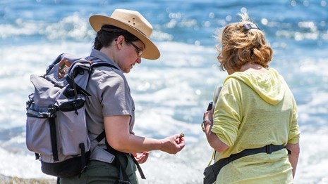 Ranger holding a small creature from a tide pool speaks with visitor