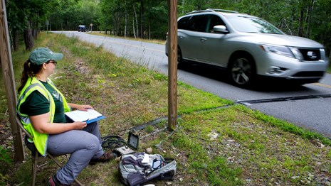 A technician seated next to road watches a car drive over a traffic monitor.
