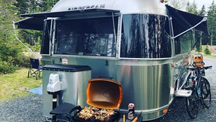 Airstream trailer with barbecue and bicycles outside