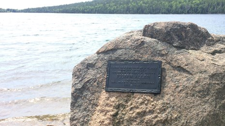 A bronze plaque on granite next to a lakeshore