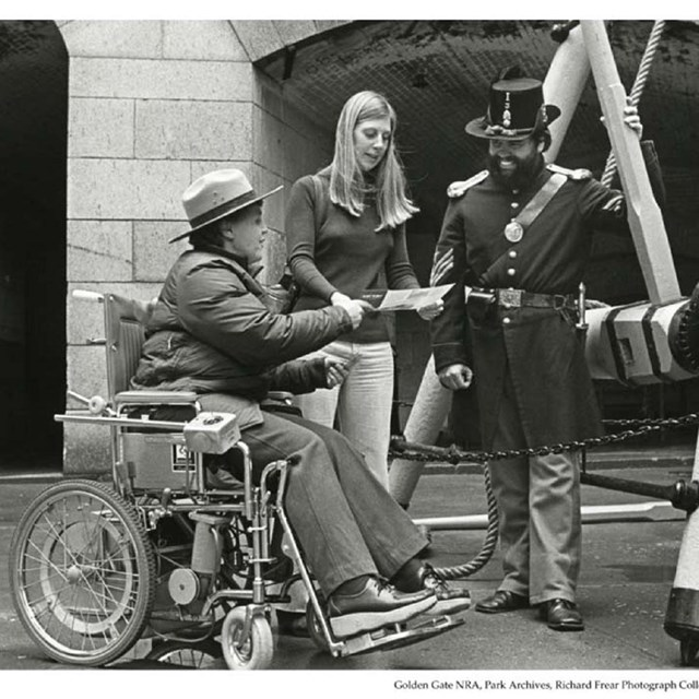Woman in wheelchair chatting with two others Golden Gate, circa 1980