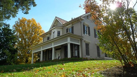 two story house with porch on a grassy hill