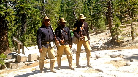 3 Buffalo Soldiers impersonators pose in front of trees