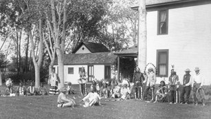 Black and white photo of a gathering of American Indians and Cook at the Agate Springs ranch house.