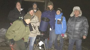 A group of visitors in winter wear enjoying a night sky program.