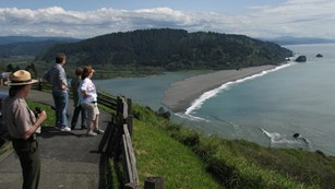 Photo of a ranger and visitors overlooking the pacific ocean from a vista in Redwood NP, CA