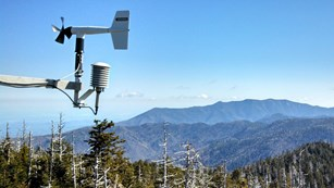 Wind vane in foreground with Smoky Mountain National Park in the background