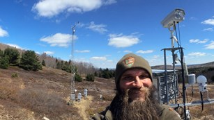 Photo of an NPS employee at the McFarland Hill air monitoring station in Acadia National Park.