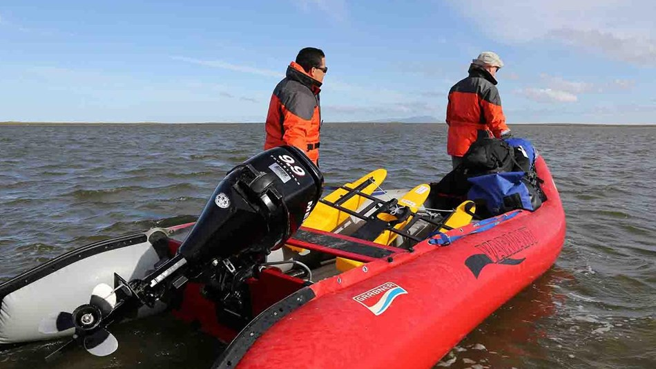 Two researchers launch a boat in an Arctic lagoon.