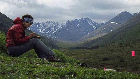 An archaeologist takes notes at a dig high in the Brooks Range.