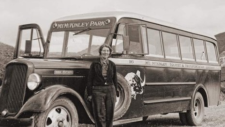 black and white historical photo of a women standing near a bus