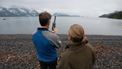 two people use a satellite phone standing on a rocky beach