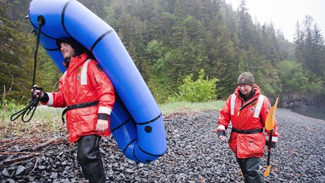 two NPS employees carry an inflatable raft along a beach in the rain