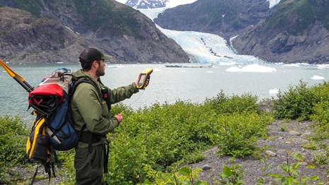 a NPS staff member takes GPS coordinates in front of a glacial lagoon