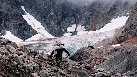a person walks through a rocky scree field in front of a small valley glacier