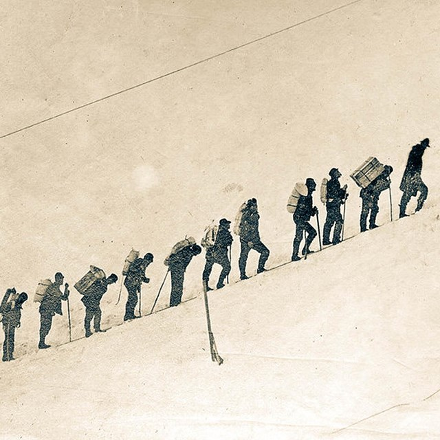 a line of hikers in the snow during the klondike gold rush