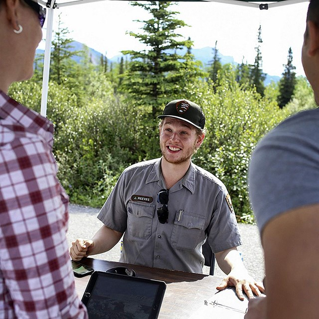 a ranger in uniform speaks to two visitors in a booth at an event in Denali national park